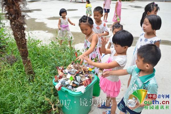 小朋友们积极参与到捡拾垃圾的队伍中,有秩序地将其扔向垃圾桶,桶内的图片